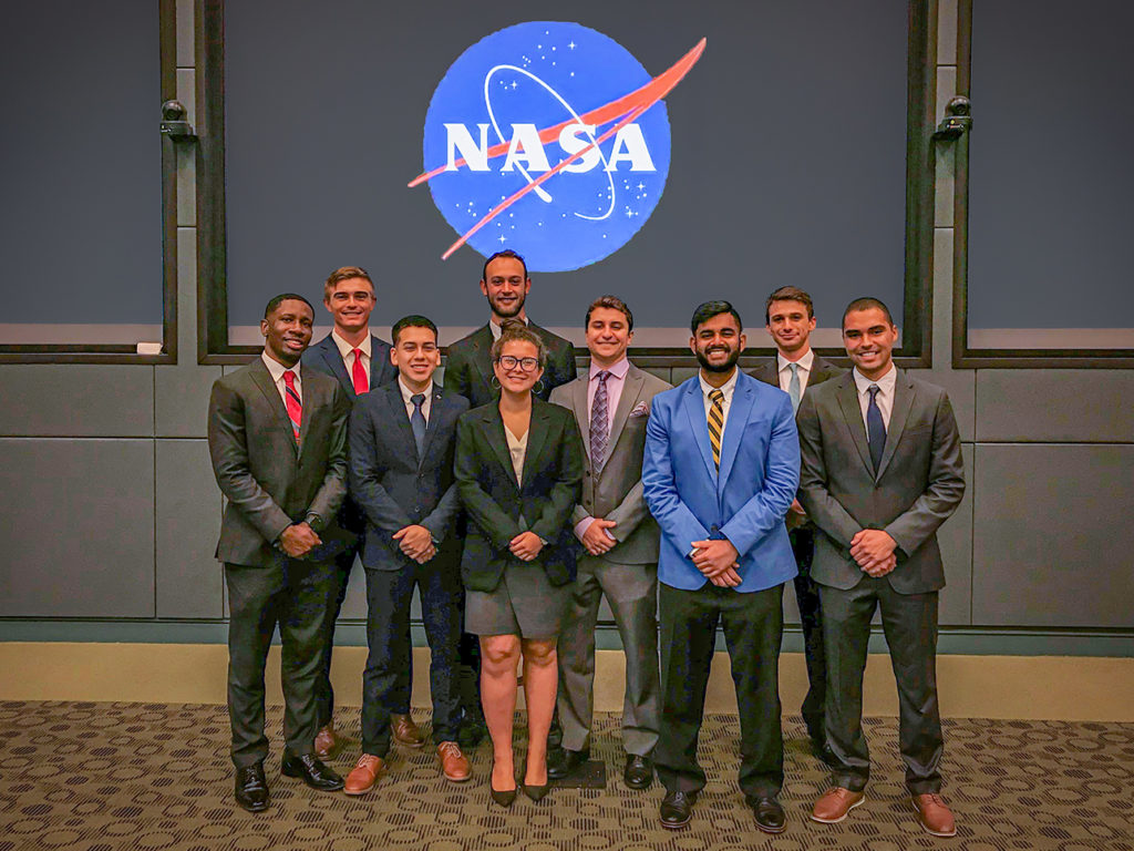 Ely and other interns pose in front of the NASA logo.