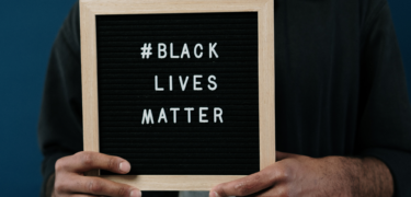 Black Lives Matter sign held by a man with his head cropped off