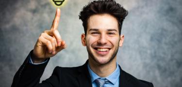 A man in a suit points to an icon of a lit up light bulb.