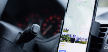 A close up of a phone propped up in a car showing Central Park in New York on Google Maps.