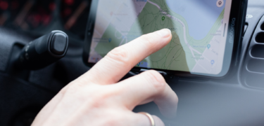 Woman touching cell phone screen map mounted in car
