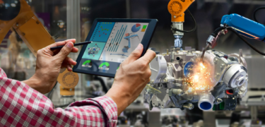 Man holding tablet while engineering machine works in the background.