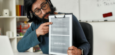 """A man points to a clipboard with a piece of paper that reads, """"JavaScript Syntax."""""""