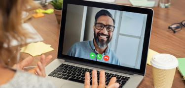 A woman video conference chats with a man.