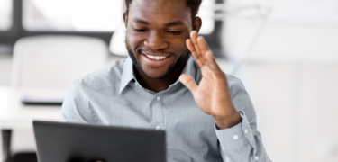 A man waving on a conference call on a tablet.