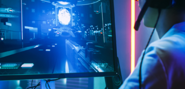 Male student with a headset playing video game on computer monitor.