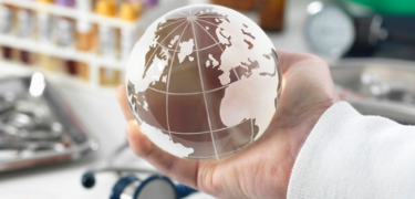 A hand with long sleeves, holding a small globe with medicinal and health-related items in the background.