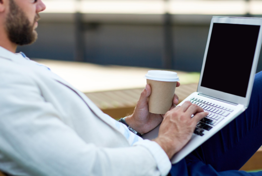 Man with his laptop on his lap with a black screen and coffee in his hand.