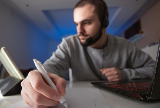 A man wearing headphones and writing on a piece of paper.