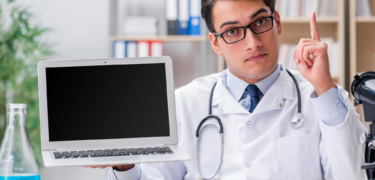 A doctor points up with one hand and holds his laptop in the other.