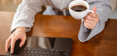 Person on their laptop with coffee in hand.