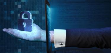 A hand extending through a laptop screen holding onto a virtual lock.