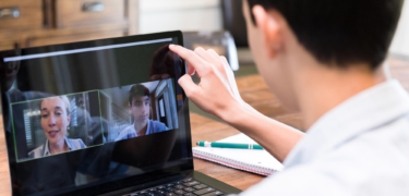 A student video conferencing on his laptop.