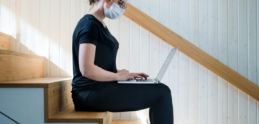Woman sitting on the stairs with a mask on and working on her laptop
