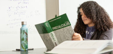 A high school student studies information in her textbook during class