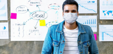 Portrait of young asian man worker wear medical mask protection looking at camera smiling under surgical mask in office workspace in concept back to work, reopen business, prevent coronavirus virus.