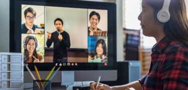 Closeup Asian woman hand writing lecture when online learning via video conference