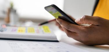A hand holding a cellphone over a table calendar.