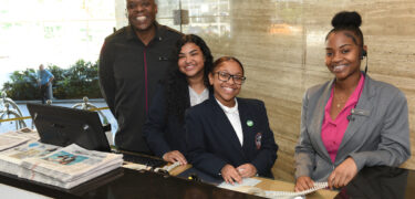 Two students and hotel staff stand behind the concierge desk.