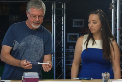 A man displays a micropipette while a woman watches.