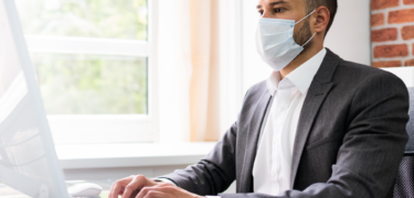 A man wearing a suit and a mask uses the computer.
