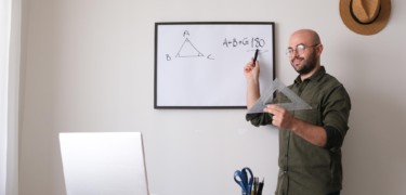 A man points to a math equation on a white board in front of his laptop.
