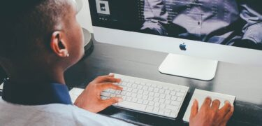 A young man typing and looking at a computer screen.