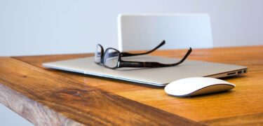 Glasses on top of a closed macbook.