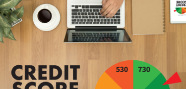 An overhead view of a person on their laptop with coffe and a credit score graph underneath.