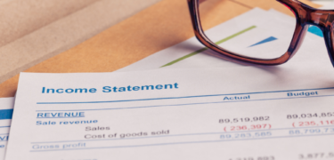 "A pair of glasses on top of a document that reads ""income statement"""