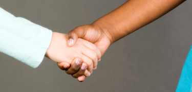 A white hand holds hand with a person of color.