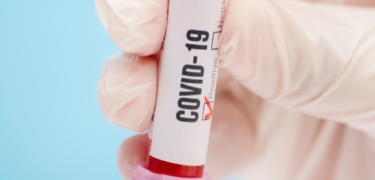 Close up of a vial of blood that reads Covid-19 and a check mark on the positive square.