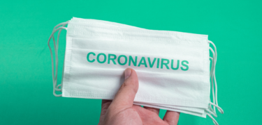 """A hand is shown holding multiple masks with the word """"Coronavirus"""" on it."""