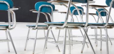 Classroom chairs facing a blackboard.