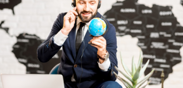 A man in a suit holds a small globe as he holds onto his headset.