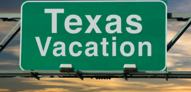 "A freeway sign reads ""Texas Vacation"" with a sunset behind it."