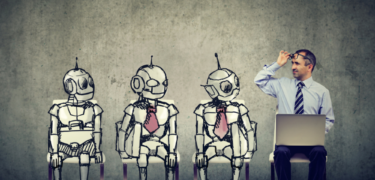 Three robots are shown sitting, weraring ties, next to a man on his laptop with a tie. He looks at the robots