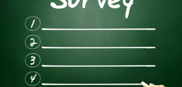 """A chalk board with the word """"Survey"""" written on it and 4 blank lines."""