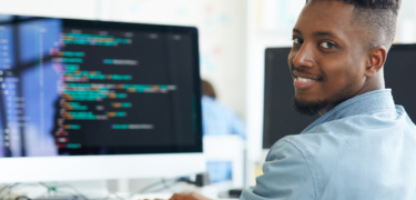A man looking at the camera. He is coding on the computer.