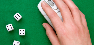 A hand on a computer mouse and 5 dice.