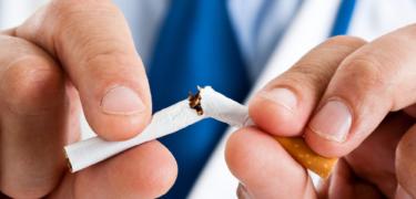 A doctor is breaking a cigarette in half.