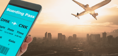 A phone is in front of a plane flying over a city.