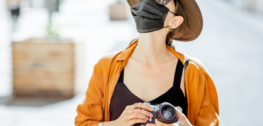 A woman travelling is wearing a mask and a hat, while holding a camera.