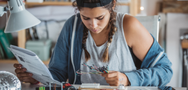 A young woman studies some wires.