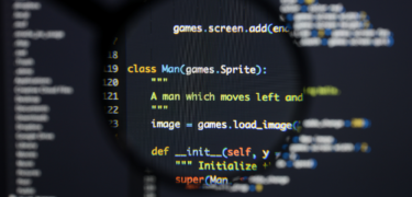 A lens zooms in on coding on a screen.
