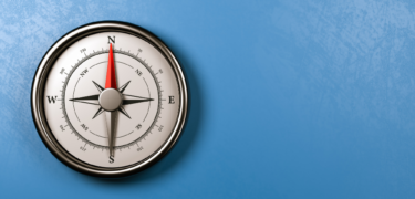 A compass sits on a blue background.
