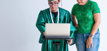 A person in their cap in gown are on their laptop with a woman standing next to them.