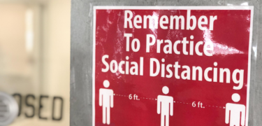 "A sign says, ""Remember to Practice Social Distancing,"" with three people rawn apart with ""6 ft."" between them."