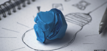 A crumpled piece of paper sits on a drawing of a lightbulb.