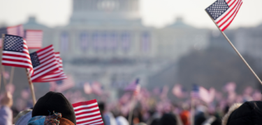 People holding flags in front of the U.S. Capitol.